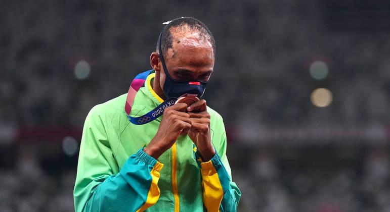 Alison beija a medalha de bronze que ganhou nos 400 metros com barreiras em Tóquio