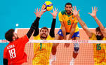 Tokyo 2020 Olympics - Volleyball - Men's Pool B - Brazil v The Russian Olympic Committee - Ariake Arena, Tokyo, Japan – July 28, 2021. Egor Kliuka of the Russian Olympic Committee in action with Bruno of Brazil and Lucas of Brazil. REUTERS/Carlos Garcia Rawlins