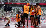 Tokyo 2020 Paralympic Games - Athletics - Women's 200m - T11 Round 1 - Heat 4 - Olympic Stadium, Tokyo, Japan - September 2, 2021. Guide Manuel Antonio Vaz da Veiga on one knee proposes to Keula Nidreia Pereira Semedo of Cape Verde in front of other athletes after competing REUTERS/Athit Perawongmetha