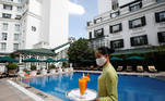 FILE PHOTO: A woman wearing a protective mask carries glasses of fruit juice by the swimming pool after the Government eased the nationwide lockdown following the coronavirus disease (COVID-19) outbreak, at the Sofitel Legend Metropole, which was the venue of the February 2019 Trump-Kim summit, in Hanoi, Vietnam June 26, 2020. REUTERS/Kham/File Photo
