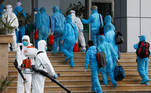 Vietnamese construction workers in blue protective suits infected with the coronavirus disease (COVID-19) arrive at the tropical diseases hospital after being repatriated from Equatorial Guinea via a specially-adapted Vietnam Airlines plane filled with medical equipment and negative pressure chambers, in Hanoi, Vietnam July 29, 2020. REUTERS/Kham