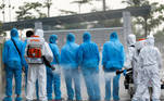 Health workers in white protective suits spray disinfectant at Vietnamese construction workers infected with the coronavirus disease (COVID-19), upon their arrival at the tropical diseases hospital after being repatriated from Equatorial Guinea via a specially-adapted Vietnam Airlines plane filled with medical equipment and negative pressure chambers, in Hanoi, Vietnam July 29, 2020. REUTERS/Kham