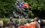 Reporters stand under the statue of a lion, decorated with a face mask, as the National Zoo reopens for socially-distanced patrons for the first time since the start of the coronavirus disease (COVID-19) outbreak in Washington, U.S. July 24, 2020. REUTERS/Jonathan Ernst
