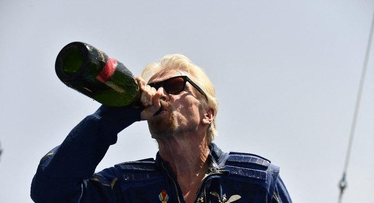 bilionário britânico Richard Branson comemora com champanhe viagem pelo espaço