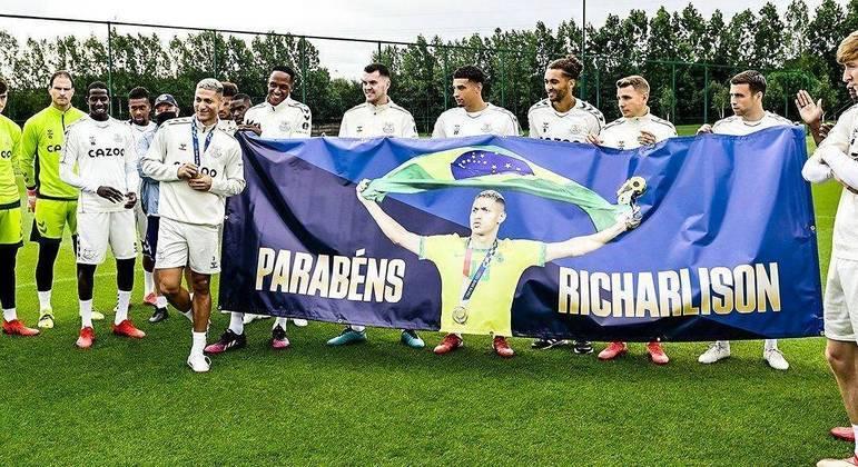 Richarlison sendo recebido pelos seus companheiros de equipe com a medalha de ouro dos Jogos de Tóquio 2020