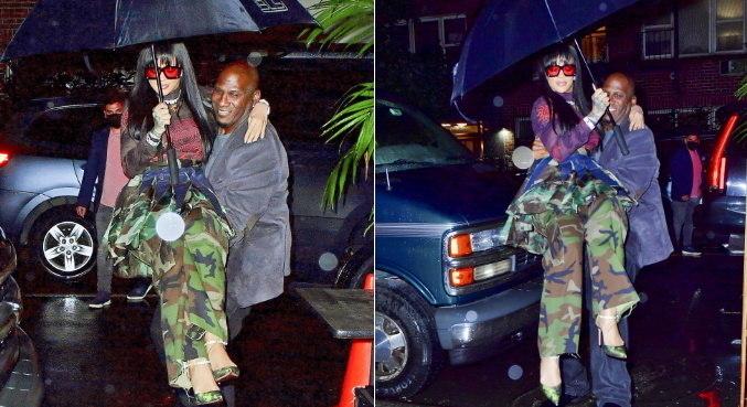 Em dia chuvoso, Rihanna precisou da ajuda do segurança para não estragar look