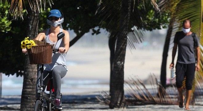 Ciclista e pedestre usam máscara em calçadão no Rio de Janeiro