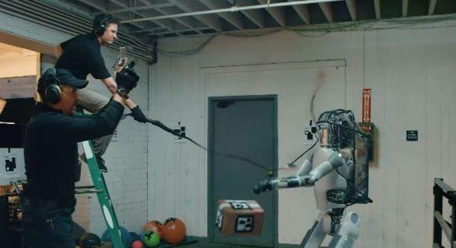 Robô tenta carregar caixa enquanto leva tiros e chicotadas