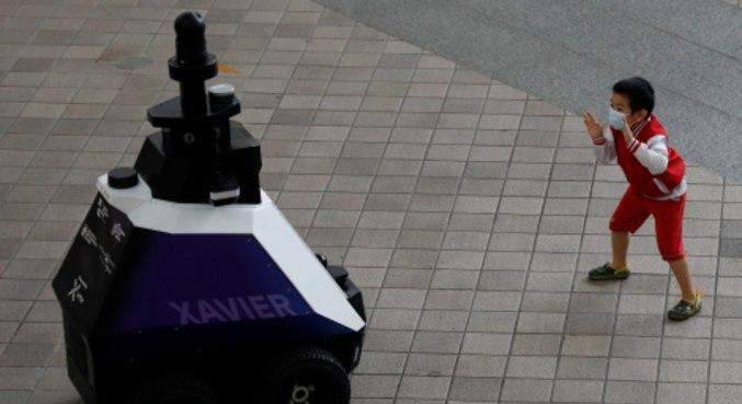 Menino brinca em frente a robô usado em Cingapura para patrulha