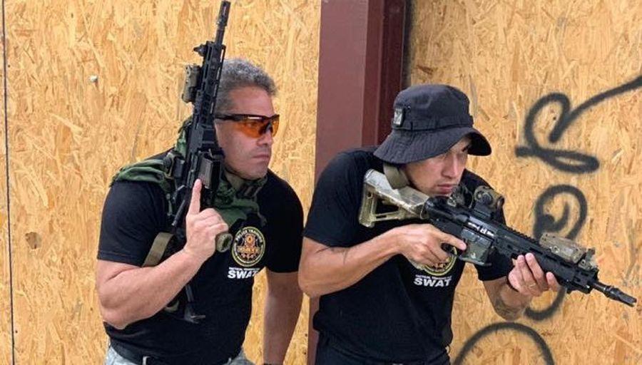 Rollo fazendo curso com a Swat. Ele está de óculos e fuzil para cima