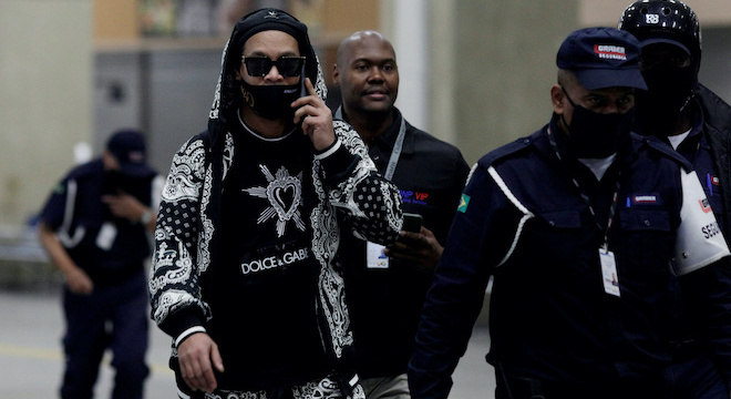 Ronaldinho desembarcou de boina, óculos escuros e máscara personalizada