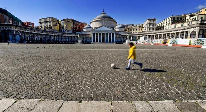 Menino joga bola em praça quase deserta em Nápoles, na Itália