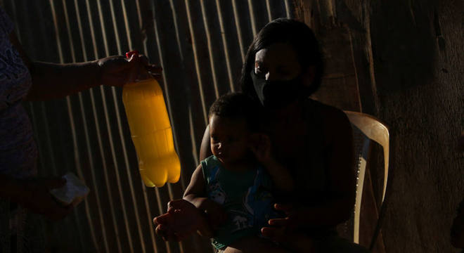 Moradora recebe um garrafa pet com detergente líquido, na Cidade Estrutural