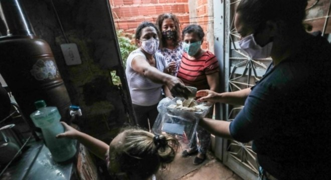 Moradora recebe sabão distribuído por  Katia Cristina, Cãdance Costa e Marisa Araújo