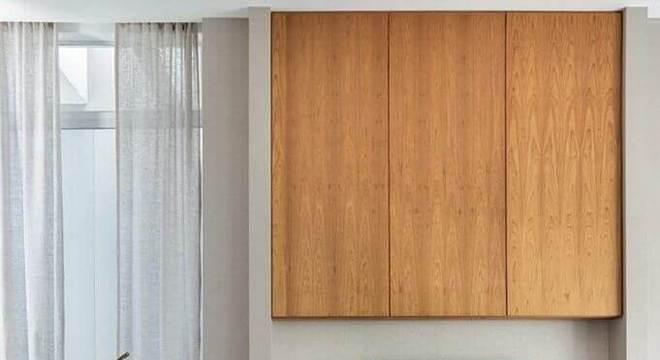 sala ampla decorada com tapete listrado e rack de madeira
