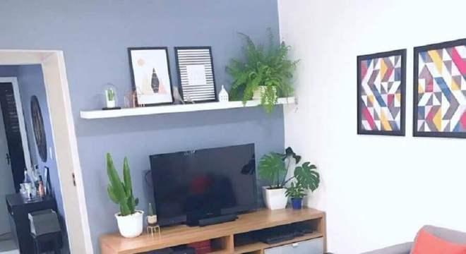 sala cinza pequena decorada com rack de madeira