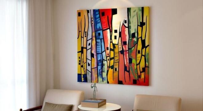 Sala de estar com mesa redonda lateral e quadro colorido Projeto de Rawi Arquitetura