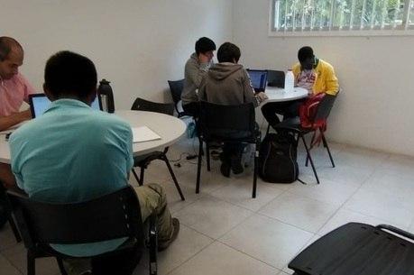 Sala de estudos com computador e mesas
