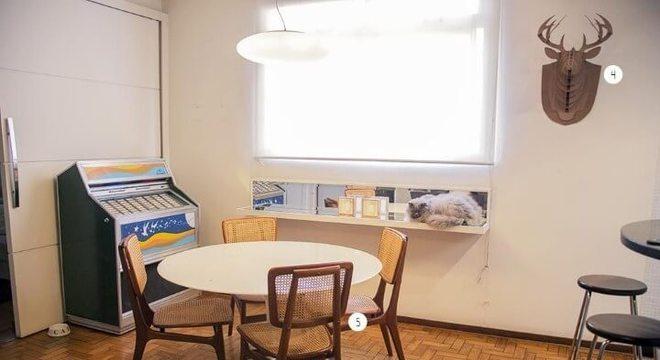 Sala de jantar com mesa redonda e 4 cadeiras de madeira e jukebox ao fundo Projeto de Casa Aberta