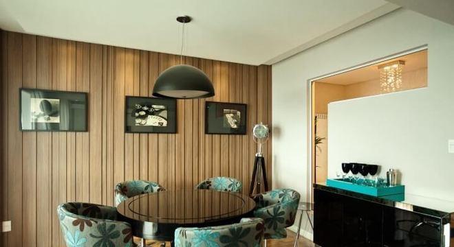Sala de jantar com mesa redonda preta e poltronas coloridas Projeto de Juliana Pippi