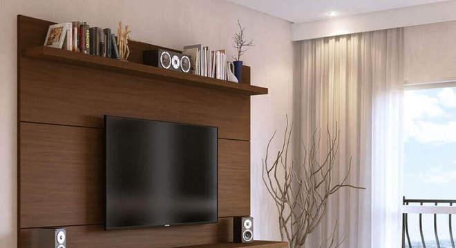 sala decorada com puff de linho e rack com painel de madeira suspenso