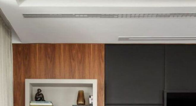 sala decorada com rack de madeira e parede com revestimento cinza