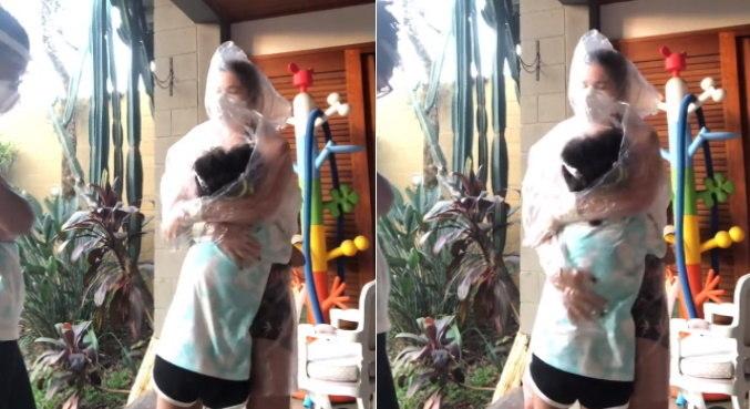 Emocionada, Samara Felippo abraçou as filhas usando uma capa de chuva