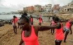 Iniciantes aprendendo a surfar com a Black Girls Surf (BGS), sentam-se em um barco enquanto se preparam para participar de uma sessão de treinamento orientada por Khadjou Sambe Sambe auxilia as iniciantes, começando o treinamento na praia e ajudando na preparação física das atletas