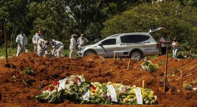 Sepultadores trabalham em covas abertas no cemitério de Vila Formosa