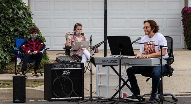 Adam Chester tocando enquanto seu filho e esposa assistem