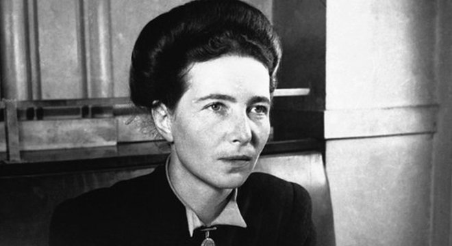 Simone de Beauvoir aparece em foto sentada e diante de uma mesa, com caneta na mão