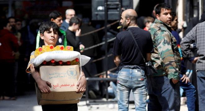 Menino carrega cesta básica distribuída em Aleppo pelo Programa de Alimentação da ONU