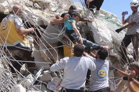 Homens resgatam criança após explosão em Idlib, na Síria
