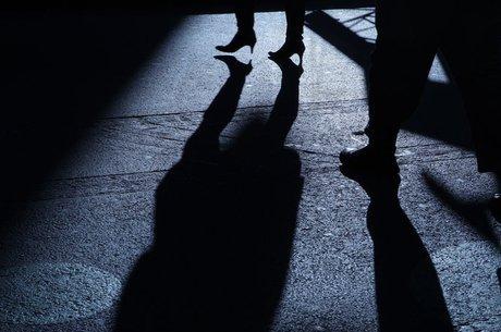 Sombra de figura masculina atrás de mulher