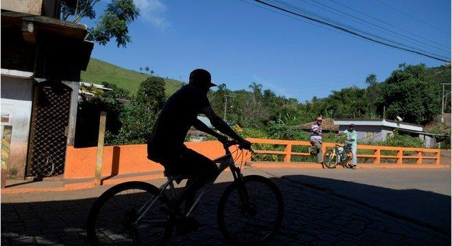 Sombra de homem passando de bicicleta em ponte de Barão de Cocais, durante dia ensolarado e observado por outros dois homens