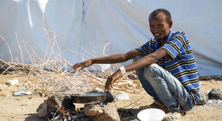 Refugiado etíope cozinha em um campo no Sudão: conflitos ajudam a piorar a situação global