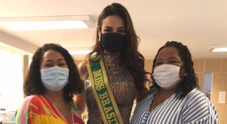 Julia Gama posa com Suéli e Nilde, usando o vestido confeccionado pelas costureiras de Paraisópolis
