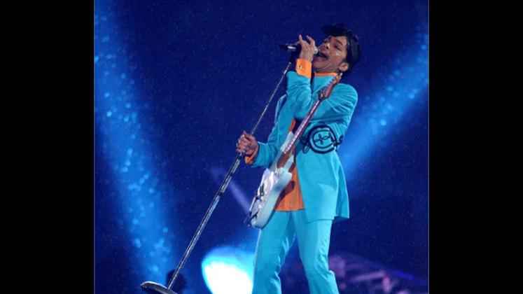 """Super Bowl XLI - Prince: O gênio do pop fez em Miami um dos mais lendários shows do halftime do Super Bowl. Sob a fortíssima chuva da Flórida, o artista e toda a produção superaram diversas dificuldades técnicas e aproveitaram a tempestade para fazer de """"Purple Rain"""" possivelmente a melhor performance da história do evento."""