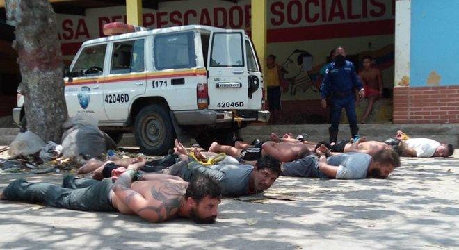 No chão, suspeitos presos em uma embarcação no povoado de Chuao