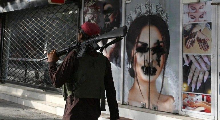 Com rifle no ombro, um talibã fazia patrulha em frente ao estabelecimento