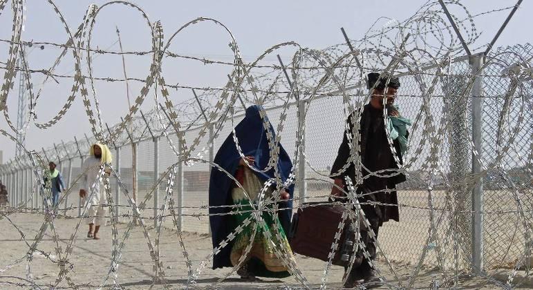 Afegãos caminham após atravessarem a fronteira com o Paquistão, na cidade de Chaman