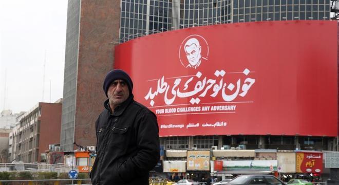 Homem caminha em frente a outdoor homenageando Qasem Soleimani