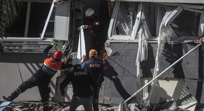 Equipe de resgate trabalham na busca por vítima em escombros de prédios