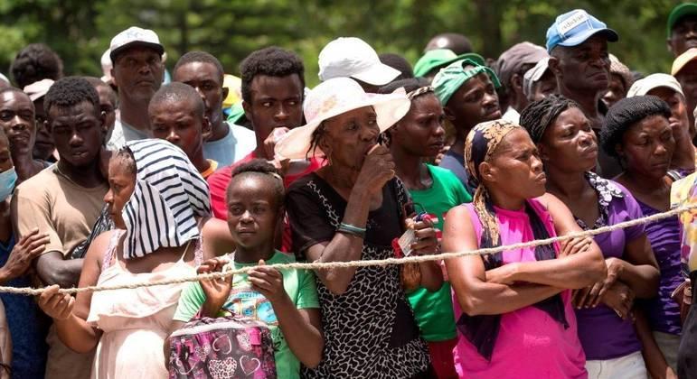 Haitianos em fila nesta sexta-feira (20) para receber doações de alimentos