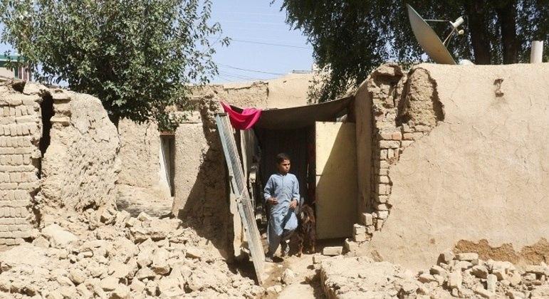 Garoto caminha em meio aos escombros após o terremoto que atingiu o Paquistão