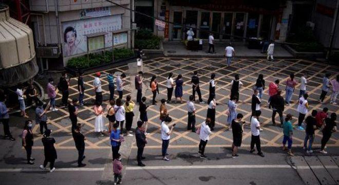 Moradores fazem fila para serem testados em Wuhan