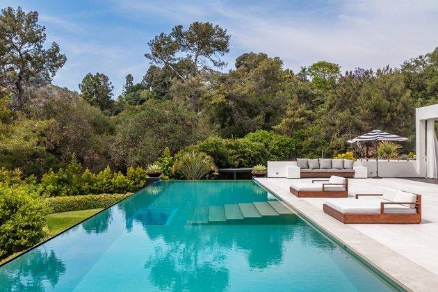 Entre as comodidades da casa está uma enorme piscina de borda infinita com cascata na área externa