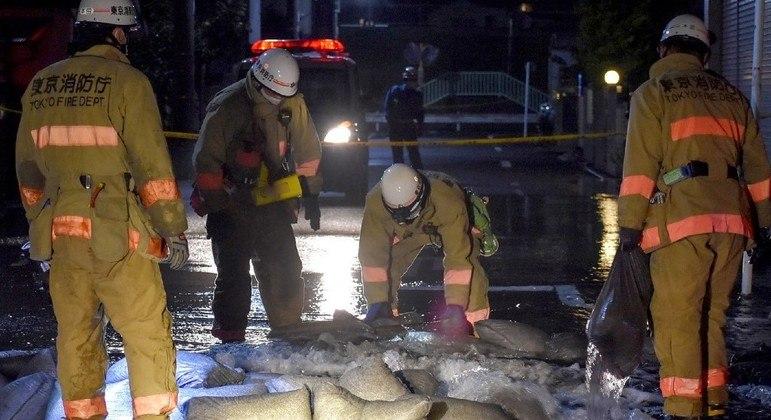Membros do Corpo de Bombeiros de Tóquio tentam consertar um cano d´água após o terremoto