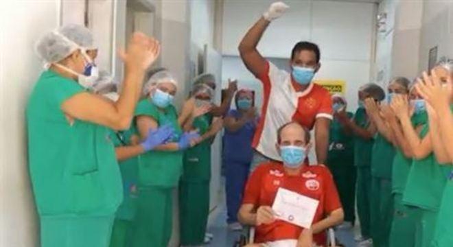 Torcedor fanático do Timbu veste vermelho e branco para celebrar alta após 30 dias de internação e é ovacionado por enfermeiras. Saiba como amor de paciente pelo Náutico ajudou no tratamento