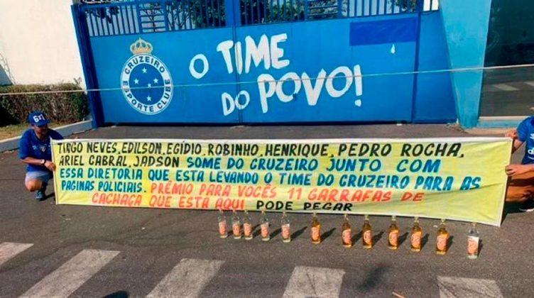 Torcedores do Cruzeiro protestam contra os medalhões do time na porta do CT e oferecem garrafas de cachaça.